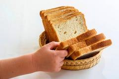 Kind, das ein Stück Brot nimmt Lizenzfreie Stockfotos