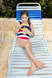 Kind, das ein tropisches Getränk an einem Pool im Freien genießt Stockfotografie