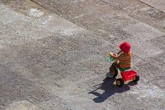 Kind, das ein trycicle reitet Stockbilder