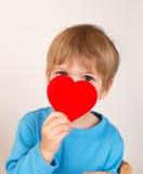 Kind, das ein Valentinstag-Herz hält stockbild