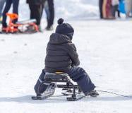 Kind, das eine Achterbahn im Winter reitet Lizenzfreie Stockfotos