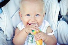 Kind, das eine Banane im schützenden Gitter isst lizenzfreie stockbilder