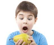 Kind, das eine Birne isst Stockbild