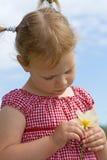 Kind, das eine Blume studiert. Lizenzfreies Stockfoto