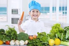 Kind, das eine Karotte beim Vorbereiten des Gemüses hält Lizenzfreie Stockbilder