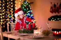 Kind, das eine Kerze am Weihnachtsessen beleuchtet stockbilder
