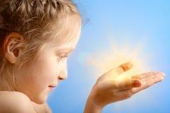 Kind, das eine Sonne anhält Lizenzfreie Stockbilder