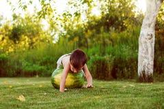 Kind, das eine Wassermelone rollt Lizenzfreies Stockfoto