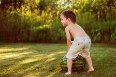 Kind, das eine Wassermelone rollt Lizenzfreie Stockfotos