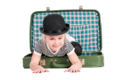 Kind, das in einem alten grünen Koffer sitzt lizenzfreies stockfoto