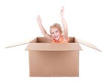 Kind, das in einem Kasten spielt Stockbild
