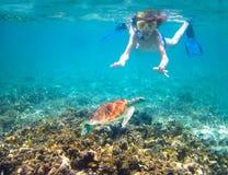 Kind, das in einem tropischen Meer nahe bei einer Schildkröte schnorchelt Lizenzfreie Stockfotos