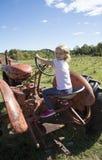 Kind, das einen alten Traktor steuert Stockbild