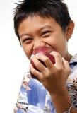Kind, das einen Apfel beißt lizenzfreie stockbilder