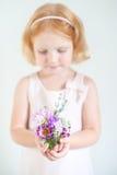 Kind, das einen Blumenstrauß von Sommerblumen hält Lizenzfreie Stockfotos