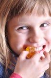 Kind, das einen Bonbon beißt lizenzfreie stockfotos