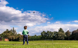 Kind, das einen Drachen im Park fliegt Stockfotos