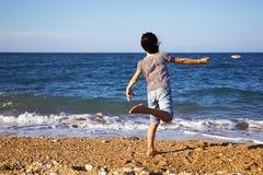 Kind, das einen Felsen wirft Lizenzfreies Stockfoto