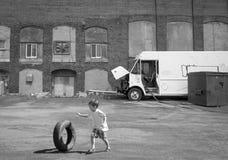 Kind, das einen Reifen rollt stockbilder