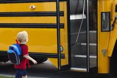 Kind, das in einen Schulbus einsteigt Lizenzfreies Stockfoto