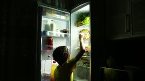 Kind, das einen Snack vor dem Kühlschrank mitten in der Nacht isst stock video footage