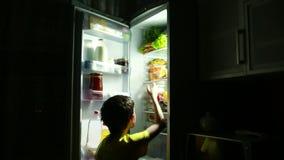 Kind, das einen Snack vor dem Kühlschrank mitten in der Nacht isst stock footage