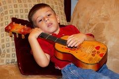 Kind, das einen Ukulele spielt lizenzfreie stockfotografie