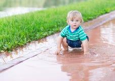 Kind, das in einer Pfütze spielt Lizenzfreie Stockfotografie