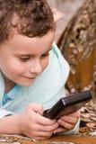 Kind, das elektronisches Spiel spielt Stockbild