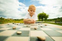 Kind, das Entwürfe oder das KontrolleurBrettspiel im Freien spielt Lizenzfreie Stockfotos