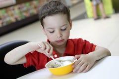 Kind, das Fleischmehlklöße mit Sauerrahm isst Lizenzfreie Stockfotos