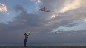 Kind, das fliegenden Drachen auf Strand bei Sonnenuntergang, glückliches kleines Mädchen auf Küstenlinie spielt lizenzfreie stockbilder