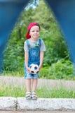 Kind, das Fußball auf einer Betondecke spielt Stockfotografie