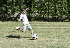 Kind, das Fußball in einem Stadion spielt Lizenzfreies Stockbild