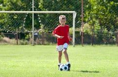 Kind, das Fußball spielt Lizenzfreie Stockfotografie