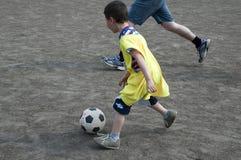Kind, das Fußball spielt Lizenzfreies Stockfoto