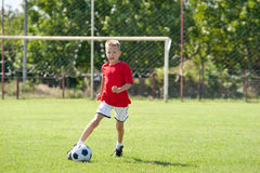 Kind, das Fußballkugel spielt Lizenzfreie Stockbilder