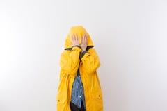 Kind, das gelbes Regen-Mantel-versteckendes Gesicht in der Haube trägt Stockfotos