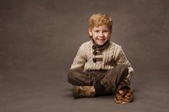 Kind, das in gestrickter Strickjacke lächelt. Jungenmode im Retrostil. Br Stockbilder