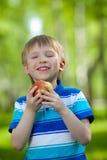 Kind, das gesunden Nahrungsmittelapfel im Freien anhält Stockbild