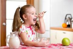 Kind, das gesundes Lebensmittel in der Küche isst Stockbild