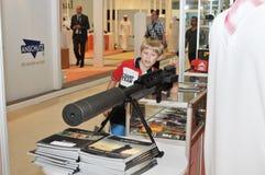 Kind, das Gewehr an Abu Dhabi International Hunting und an Reiterausstellung 2013 überprüft Lizenzfreie Stockfotografie