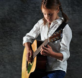Kind, das Gitarre gegen Schmutz ruinierte Wand spielt Lizenzfreie Stockbilder