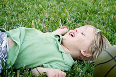 Kind, das in Gras mit dem Basketballlachen legt Stockfotografie