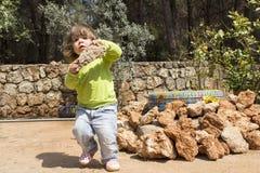Kind, das großen Felsen im Garten carying ist Stockbild