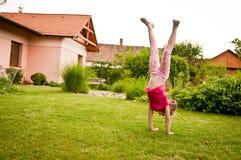 Kind, das Handstand im Hinterhof tut stockfotos