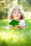 Kind, das eco Haus hält stockbild