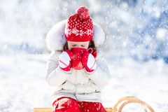 Kind, das heiße Schokolade im Winterpark trinkt Kinder im Schnee auf Chr stockfotos