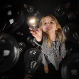 Kind, das helle Glühlampe auf schwarzem Hintergrund hält Stockfoto