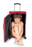 Kind, das heraus roten Koffer schaut Stockfotografie